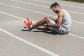 mladý běžec s zranění nohy sedící na podlaze Běžecká stopa