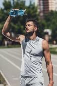Fotografie sportovní mladý muž vylévá vodu na sebe po tréninku