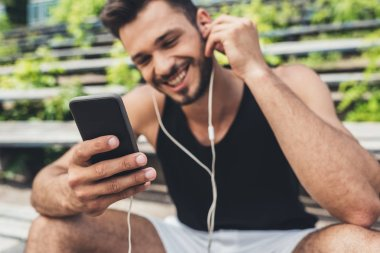 happy young man listening music with smartphone and earphones