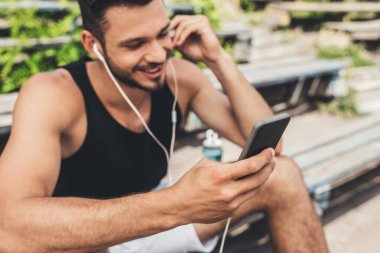 smiling young man listening music with smartphone and earphones on bench