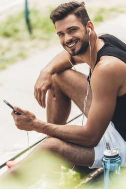young smiling man with bottle of water listening music with smartphone and earphones on bench