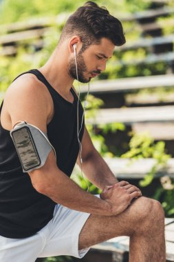 young sportsman in earphones with smartphone in running armband case doing exercise