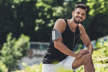 smiling sportsman in earphones with smartphone in running armband case doing exercise