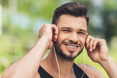 portrait of young man listening music with earphones