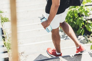 cropped image of sportsman holding bottle of water on stairs at sport playground