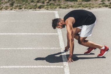serious young male athlete on low start on running track