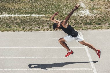 high angle view of male sprinter taking off from low start on running track