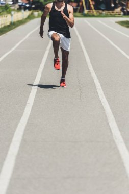 cropped shot of male athlete jogging on running track at sport playground