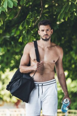 serious young man with bag for sport equipment and fitness bottle walking under green tree