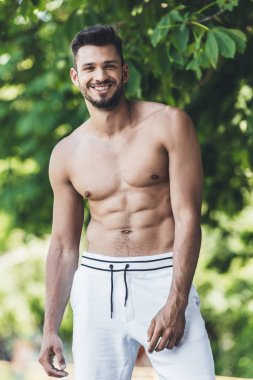 happy shirtless young man looking at camera in front of green leaves
