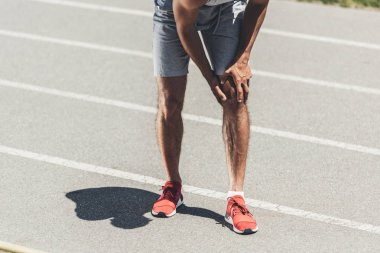 cropped shot of runner with knee injury on running track