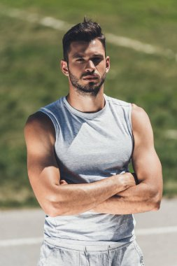 handsome young man in sportswear looking at camera with crossed arms
