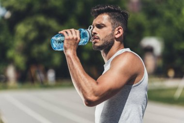 sporty young man drinking water after workout