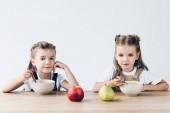 rozkošný usmívající se školačky jíst obiloviny s ovoce k snídani izolované na bílém
