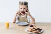 entzückende kleine Schulmädchen essen Toast mit Marmelade isoliert auf weiß