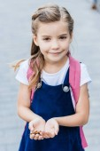 Photo adorable little schoolgirl holding butterfly in hands and looking at camera