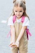 Photo adorable little child with backpack holding butterfly in hands