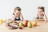 smutné, sestřičky nechtějí jíst zdravou snídani izolované na bílém