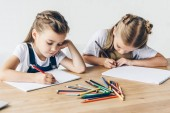 Fotografie concentrated little schoolgirls drawing with colorful pencils in albums together isolated on white