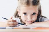 kis iskolás színes ceruza rajz és látszó-on fényképezőgép, elszigetelt fehér közeli portréja