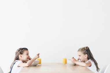 adorable smiling schoolgirls eating cereals with orange juice for breakfast while sitting in front of each other isolated on white
