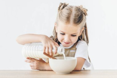 happy little schoolgirl pouring milk into cereal for breakfast isolated on white