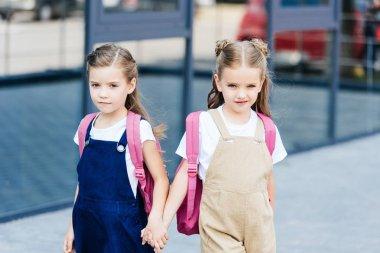 schoolgirls with pink backpacks holding hands on street