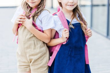 cropped shot of smiling schoolgirls with pink backpacks standing on street