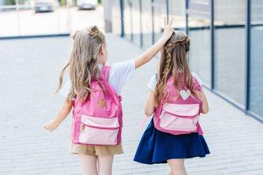rear view of little schoolgirl making horns joke gesture to her classmate on street