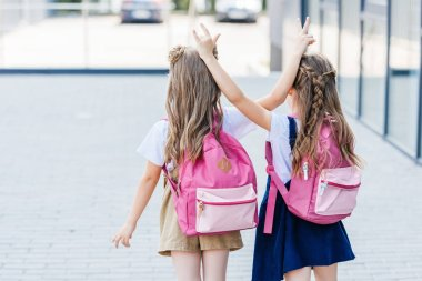 back view of little schoolgirls making horns gesture to each other on street