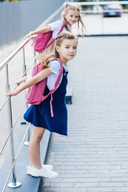 little schoolgirls with pink backpacks playing on street
