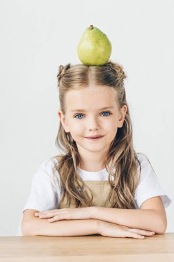 happy little schoolgirl with ripe pear on head isolated on white