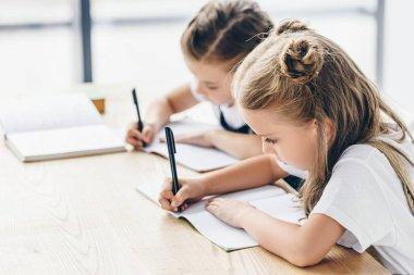 little schoolgirls writing in notebooks while doing homework isolated on white