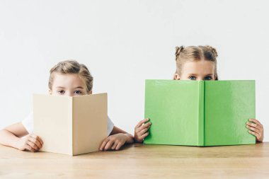 little schoolgirls covering faces with books isolated on white