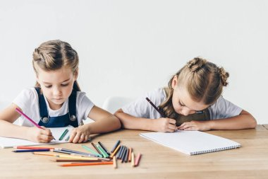 adorable little schoolgirls drawing with colorful pencils in albums together isolated on white