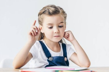 creative little schoolgirl having idea during drawing isolated on white