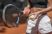 Oříznout záběr sportovní mladé ženy s tenisovou raketu a míček