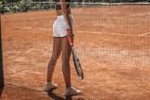 Oříznout záběr sportovní ženy s stojící raketa tenis na kurtu