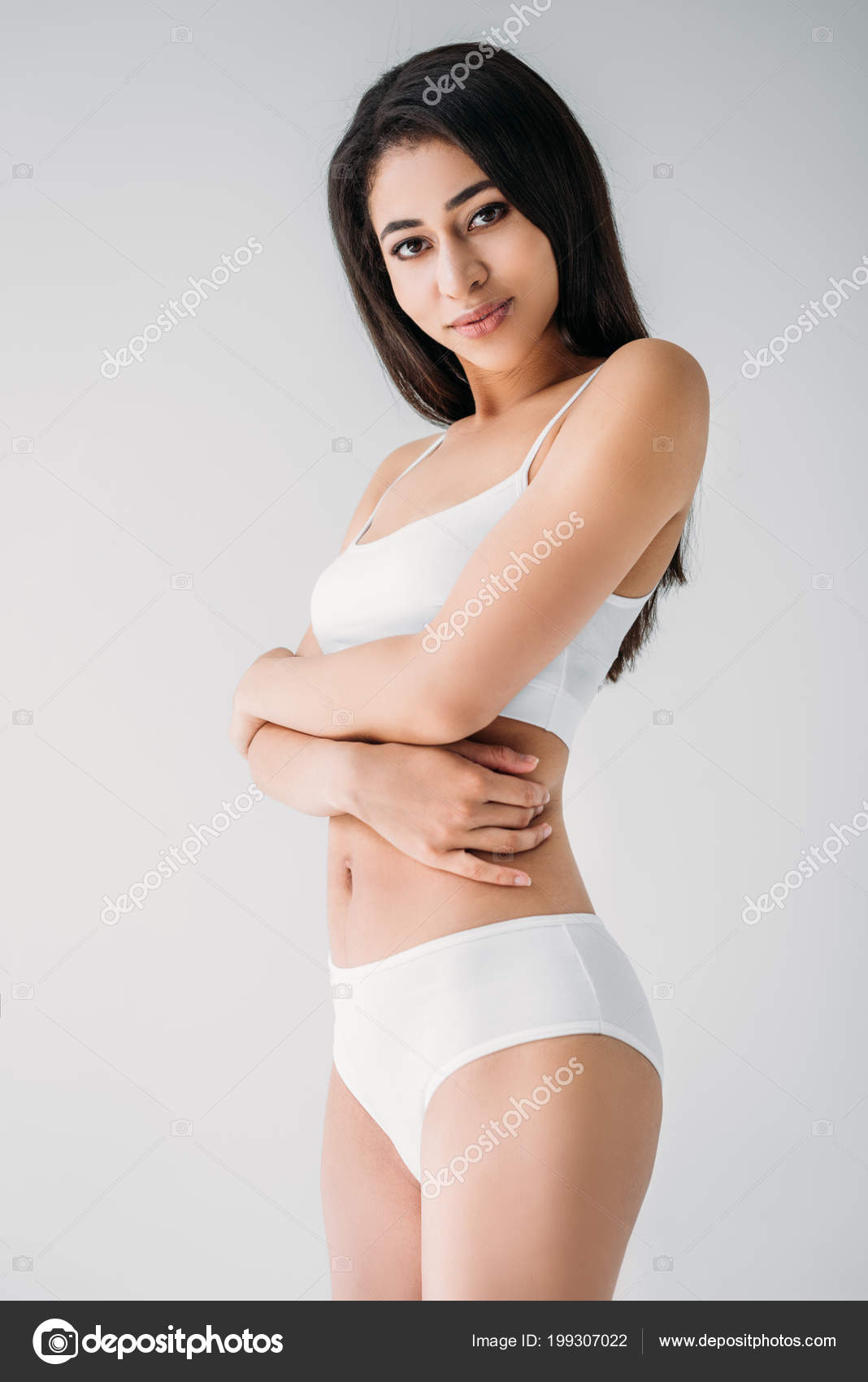 c67194f505 Attractive mixed race woman in white lingerie with crossed hands isolated  on gray background– stock image