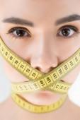 portrét atraktivní mladé ženy s uzavřenému ústa páskou měření izolované na šedém pozadí