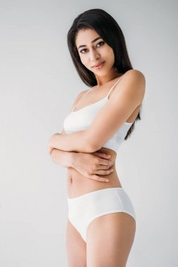 attractive mixed race woman in white lingerie with crossed hands isolated on gray background