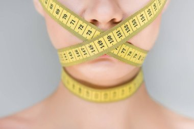 cropped image of woman with closed mouth by measurement tape isolated on gray background