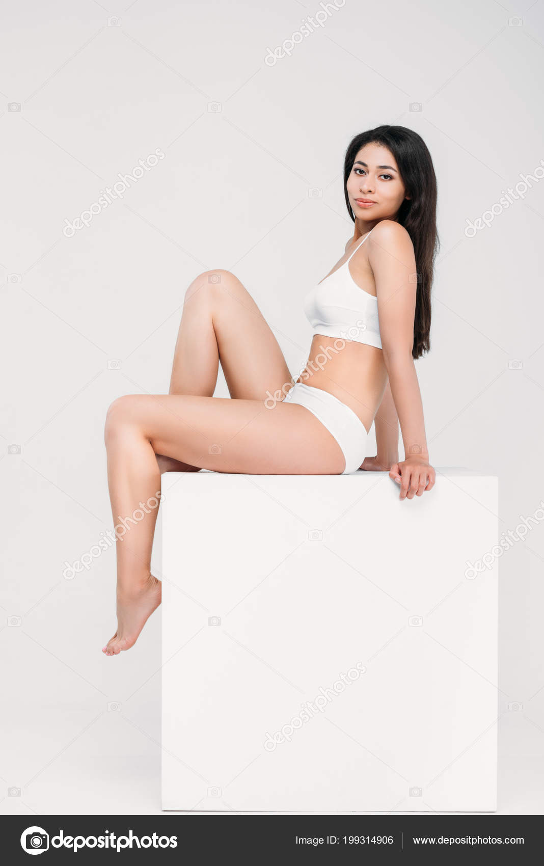c50b7cc38e76 Beautiful african american woman posing in underwear on white cube,  isolated on grey– stock image