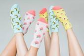 Fotografie částečné pohled na ženské nohy v barevné ovocné ponožky, izolované Grey