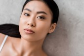 Photo portrait of lovely asian girl looking at camera, on grey