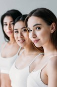 Photo beautiful multiethnic girls looking at camera, isolated on grey