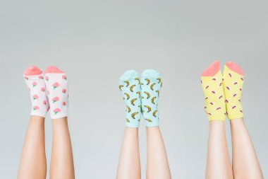 cropped image of female legs in different colorful socks isolated on gray background