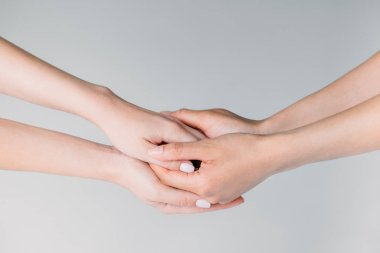 partial view of female friends holding hands, isolated on grey
