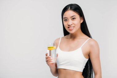 elegant asian girl in bra holding glass of water, isolated on grey