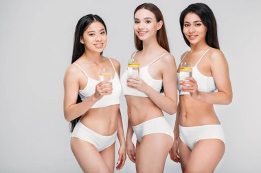 elegant multicultural girls holding glasses with lemon water, isolated on grey, healthy lifestyle